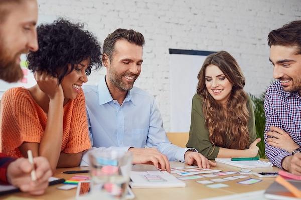 Ein Team in einem Büro sichtet Notizen zum Management für kreative Projekte auf einem Tisch.
