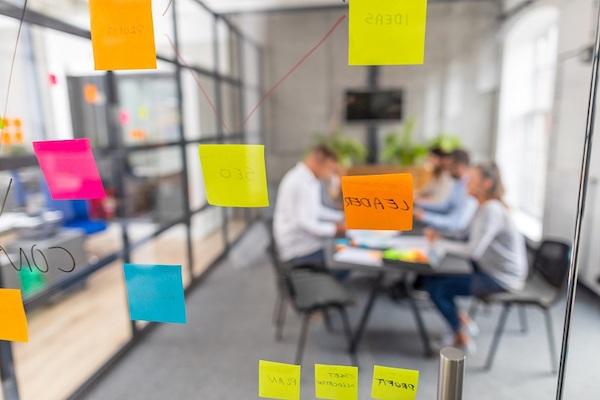 Eine Gruppe von Mitarbeitern bei der Arbeit, betrachtet durch eine transparente Wand.