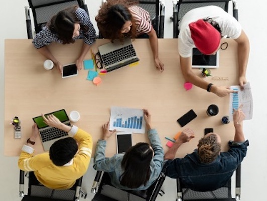 Eine Gruppe von Mitarbeitern sitzt an einem Tisch und studiert Dokumente.