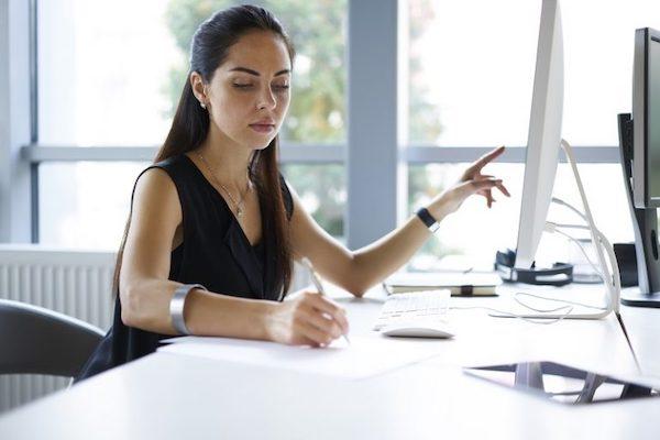 Eine junge Mitarbeiterin notiert sich etwas von ihrem Monitor zum Thema Metadaten-Editor.