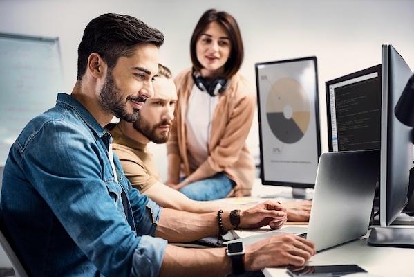 Zwei männliche Kollegen und eine weibliche Kollegin arbeiten mit verschiedenen Computern an der Erstellung von Grafiken.