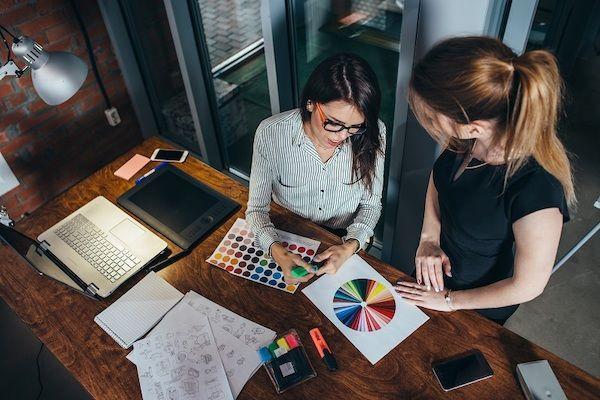 Zwei Mitarbeiterinnen sitzen an einem Tisch neben einem Laptop und überprüfen Grafiken für eine Pattern Library.