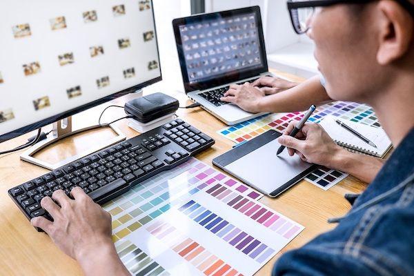 Ein junger Mann recherchiert Bilder und Designs für eine Pattern Library an einem PC.