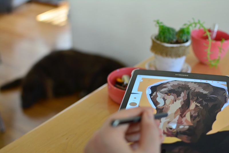 A person drawing a dog on a tablet.