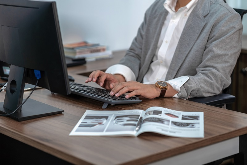 A worker types on a keyboard while referring to a magazine.