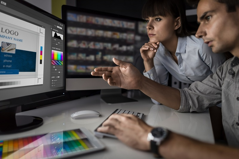 A man and woman look at a design template on a computer.