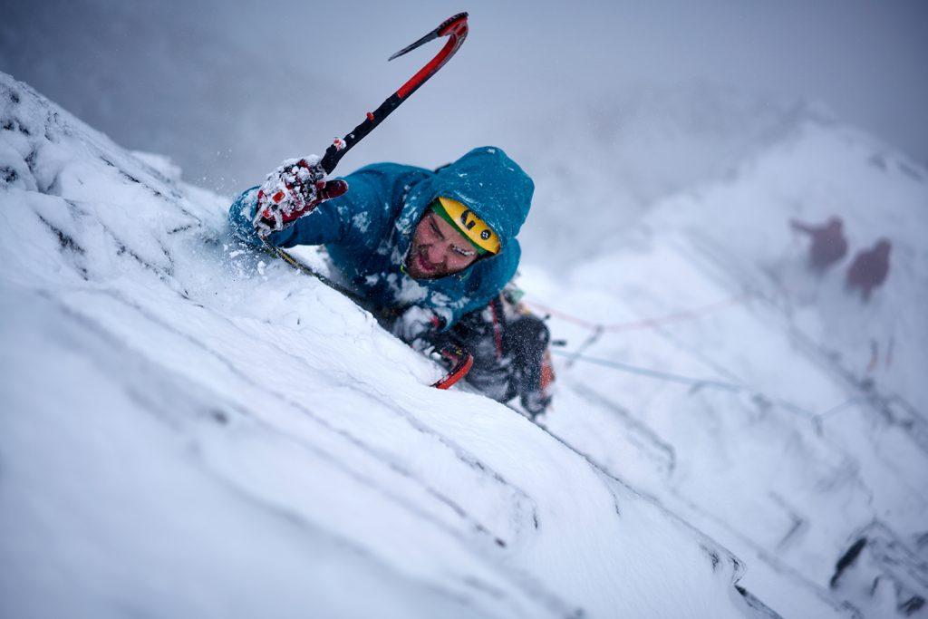A man climbing a frozen mountainside.