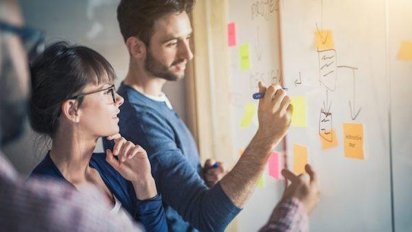 Männliche und weibliche Kollegen arbeiten an einem Whiteboard an Ideen zum Collaborative Design.