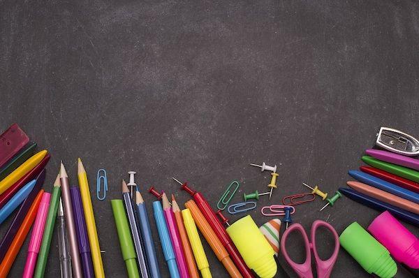 Eine Reihe von Stiften neben einer leeren Tafel.