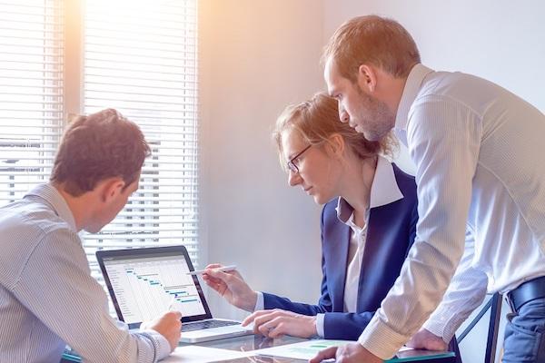 Eine Gruppe von Mitarbeitern recherchiert Daten mithilfe eines Laptops.