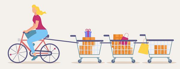 Eine Frau auf einem Fahrrad zieht eine Reihe von Einkaufswagen hinter sich her.