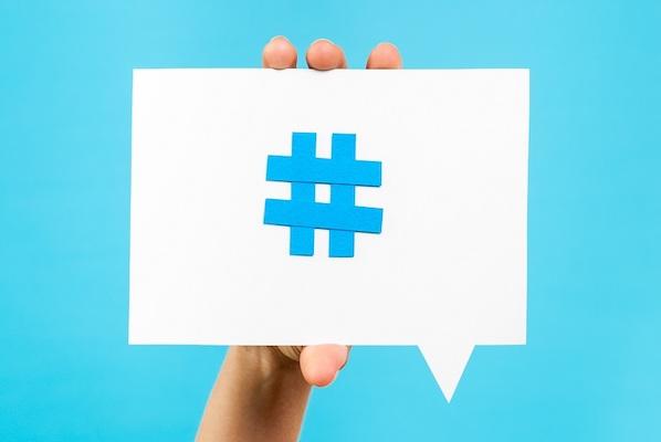 Abbildung einer Hand, die eine Karte mit einem Hashtag-Symbol von Twitter hochhält.