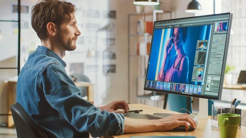 A graphic designer works on a computer on a desk.