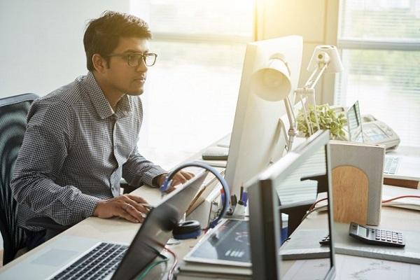 Ein Mann arbeitet an mehreren Computern.