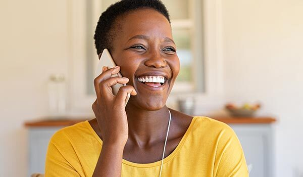 A woman smiling while on the phone.