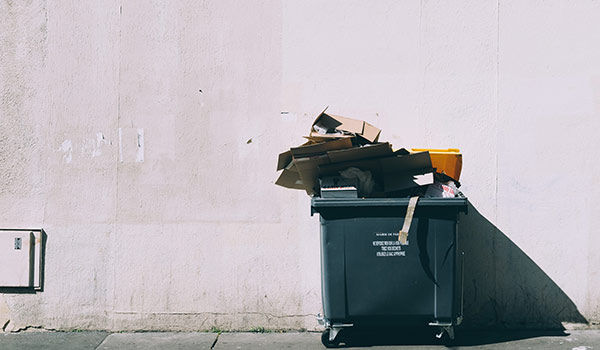 Ein Müllcontainer in einer Gasse.