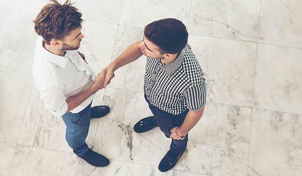 Zwei junge Männer schütteln sich die Hand, als Symbol dafür, dass Aufrichtigkeit ein Grundbaustein für Markenauthentizität ist.