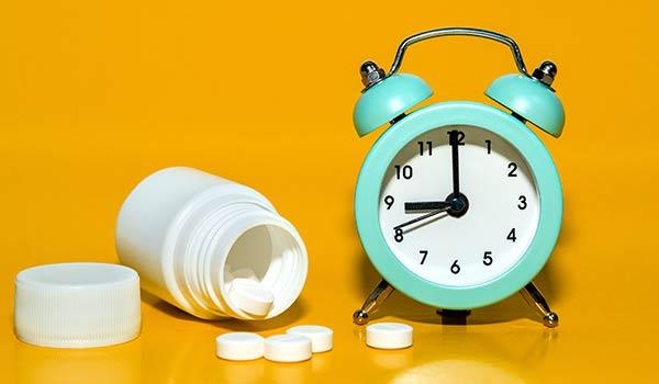 Eine Dose Tabletten neben einem Wecker.