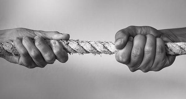 Zwei Personen ziehen an einem Seil.