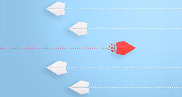 Ein roter Papierflieger, der in entgegengesetzter Richtung zu allen anderen fliegt.