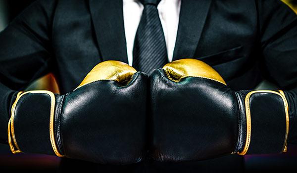 Ein Geschäftsmann im Anzug, der Boxhandschuhe trägt; er steht als Symbol für Aktionsbereitschaft, die für ein Rebranding notwendig ist.