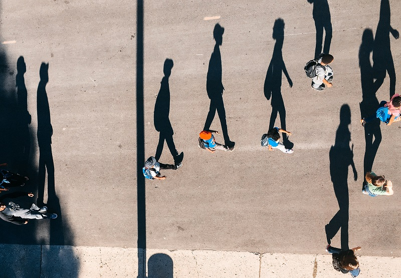 Kids walking down the street with large shadows showing.