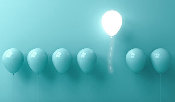 Balloons with one lit up like a lightbulb.