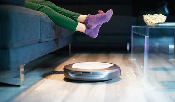 A person lifting their feet above a robot vacuum.