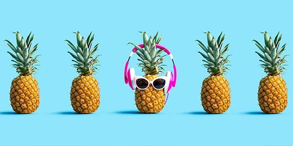 A pineapple wearing sunglasses and headphones.