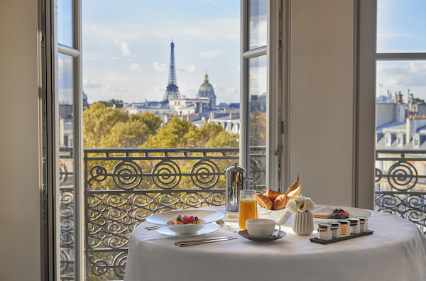 A breakfast table set in front of an open window with the Eiffel tower in Paris in the back.