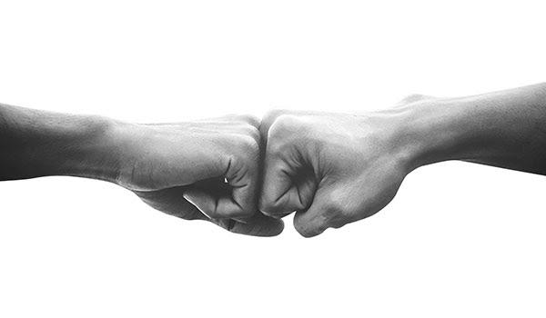 Zwei Fäuste, die miteinander anstoßen.