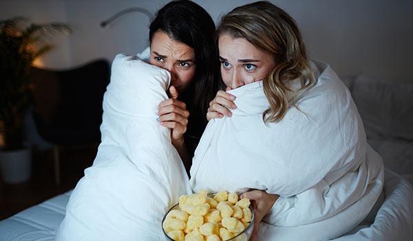 Zwei Frauen sehen sich einen Gruselfilm an.