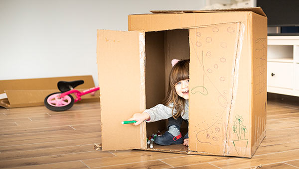 Ein junges Kind spielt in einem Karton.