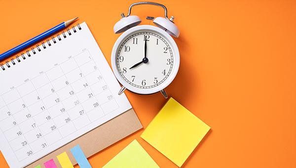 Auf einem Schreibtisch steht ein Wecker neben einem Kalender.