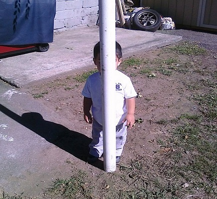 Ein Kind versteckt sich hinter einem Mast.