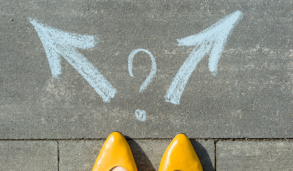 Eine Person muss sich anhand von Kreidepfeilen entscheiden, welchen Weg sie einschlagen will.