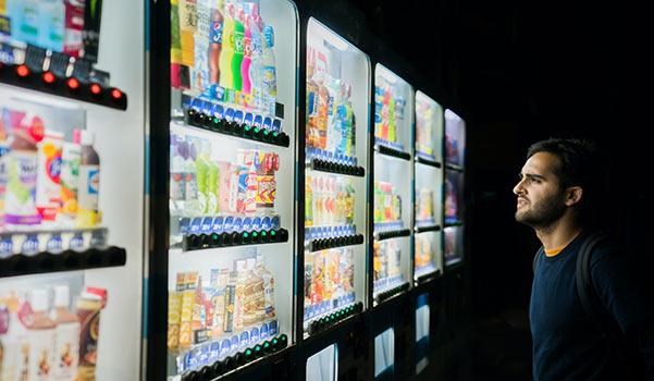 Ein Kunde steht vor einer Reihe Verkaufsautomaten und sucht sich etwas zum Essen aus.
