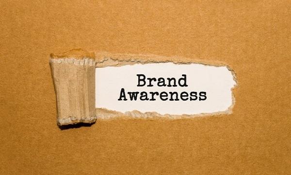 Ein Pappschild, auf dem das Wort Markenbekanntheit steht.
