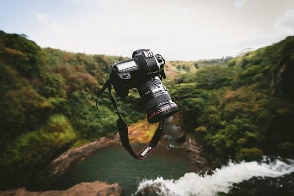 Eine Kamera von Canon schwebt über einem Bach.