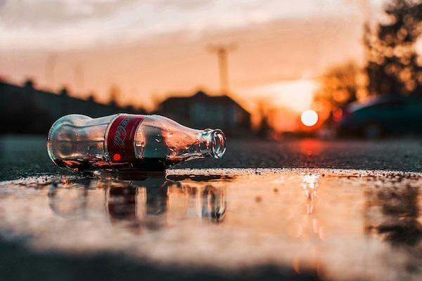 Eine Colaflasche liegt in einer Pfütze.