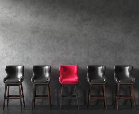 Zwischen mehreren dunklen Stühlen steht ein roter Stuhl.