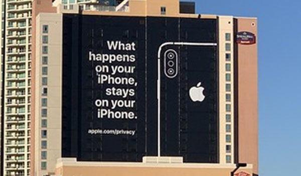 Eine Werbeanzeige für das iPhone an der Fassade eines hohen Gebäudekomplexes.