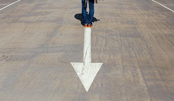 Eine Person steht am Ende eines gemalten Pfeils.
