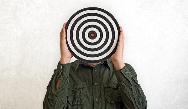 Eine Person hält sich eine Zielscheibe vor den Kopf.