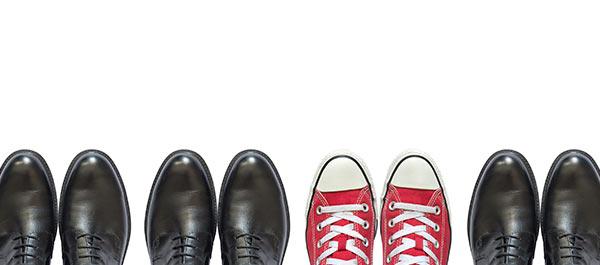 Zwischen schwarzen Schuhen steht ein Paar rote Schuhe.