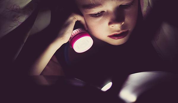 Ein kleines Kind liest mit einer Taschenlampe ein Buch.