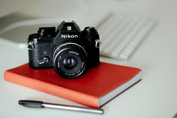 Eine Nikon-Kamera liegt auf einem Tagebuch.