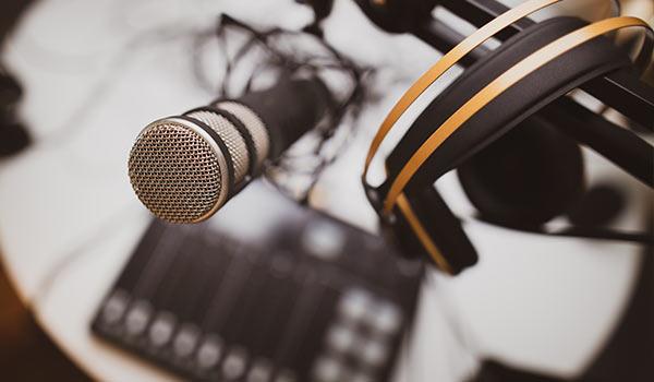Ein Mikrofon steht auf einem Schreibtisch, daneben hängen Kopfhörer.