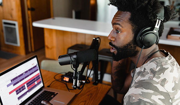 Ein junger Mann zeichnet mit seinem Laptop einen Podcast auf.