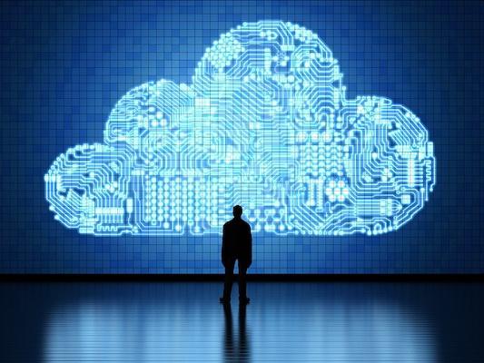 Eine Person steht vor einer großen digitalen Wolke.